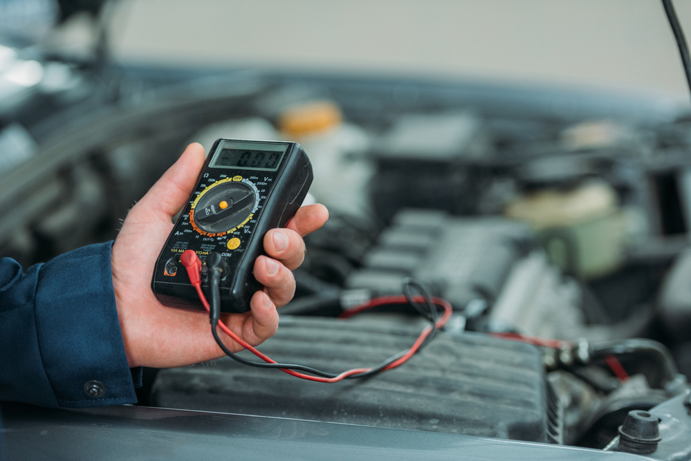 image of a hand holding a meter taking a diganostic reading of a car battery