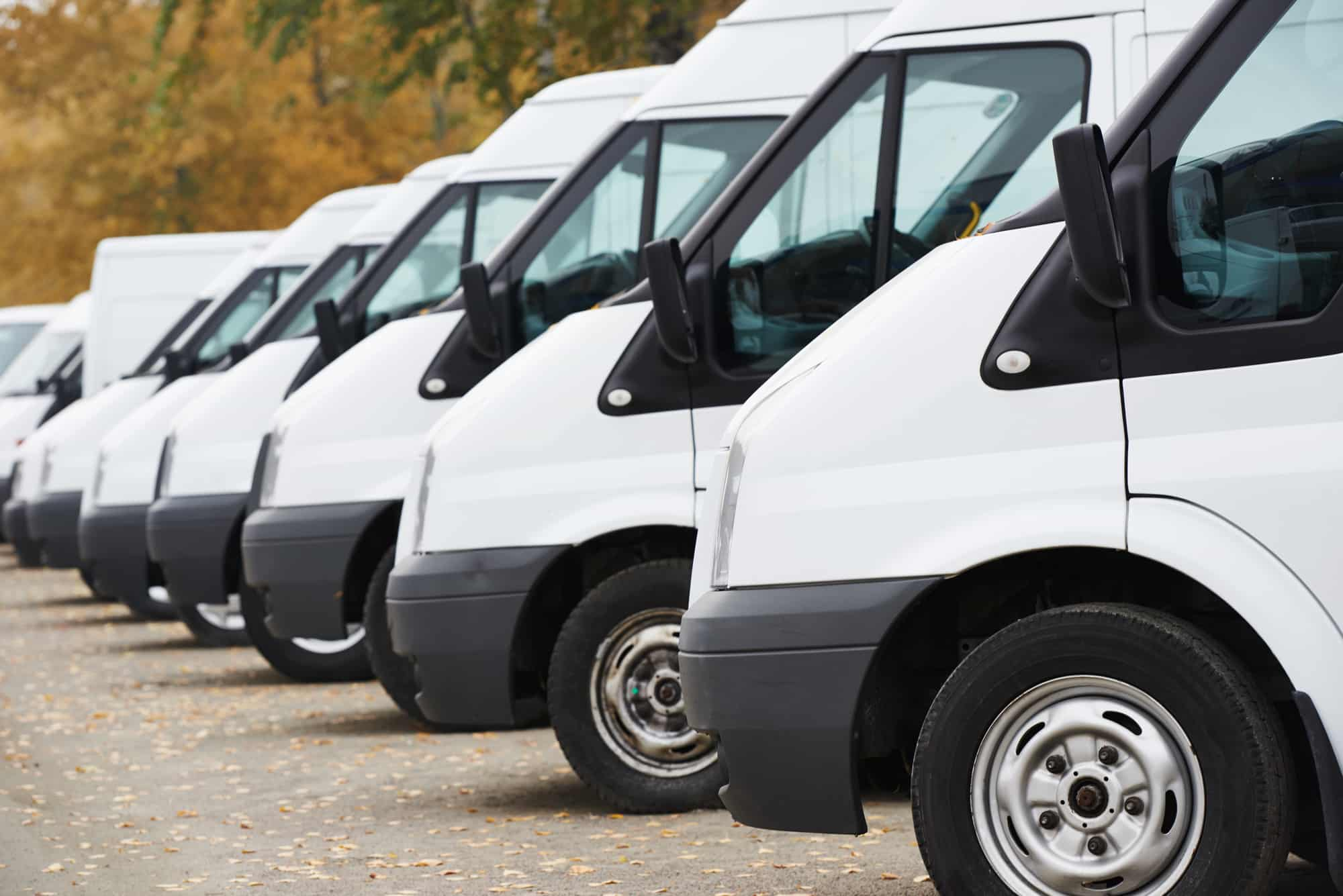 image of a fleet of white vans all in a row