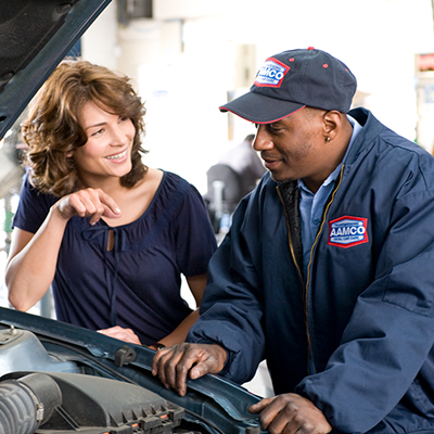 Brown haired woman and AAMCO technician looking under the hood of a car