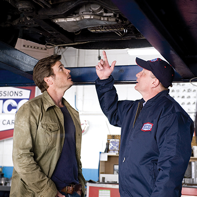 A man and an AAMCO technician looking at the underside of a car on a lift