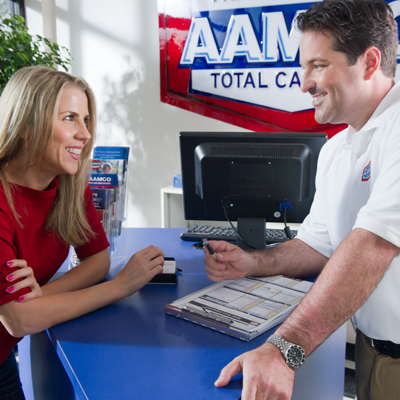 Blonde haired woman talking to an AAMCO technician at a desk