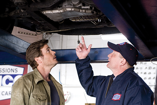 image of a man and and AAMCO technician looking at the underside of a car on a lift