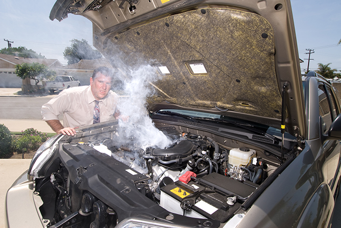 man in a white shirt leaning over the open hood of a steaming car
