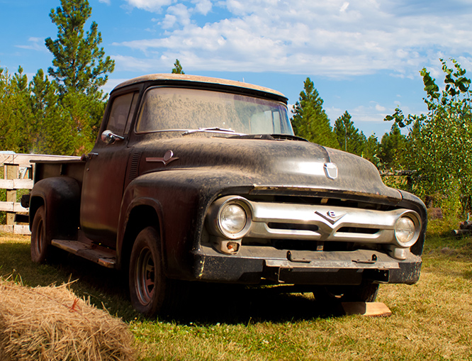 old rusted work truck in the grass