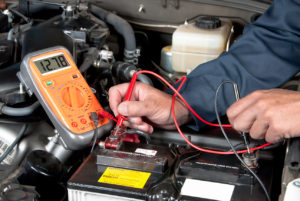 An auto mechanic uses a multimeter voltmeter to check the voltage level in a car battery