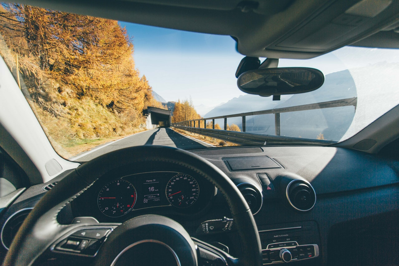view from car windshield of car driving on road surrounded by fall trees