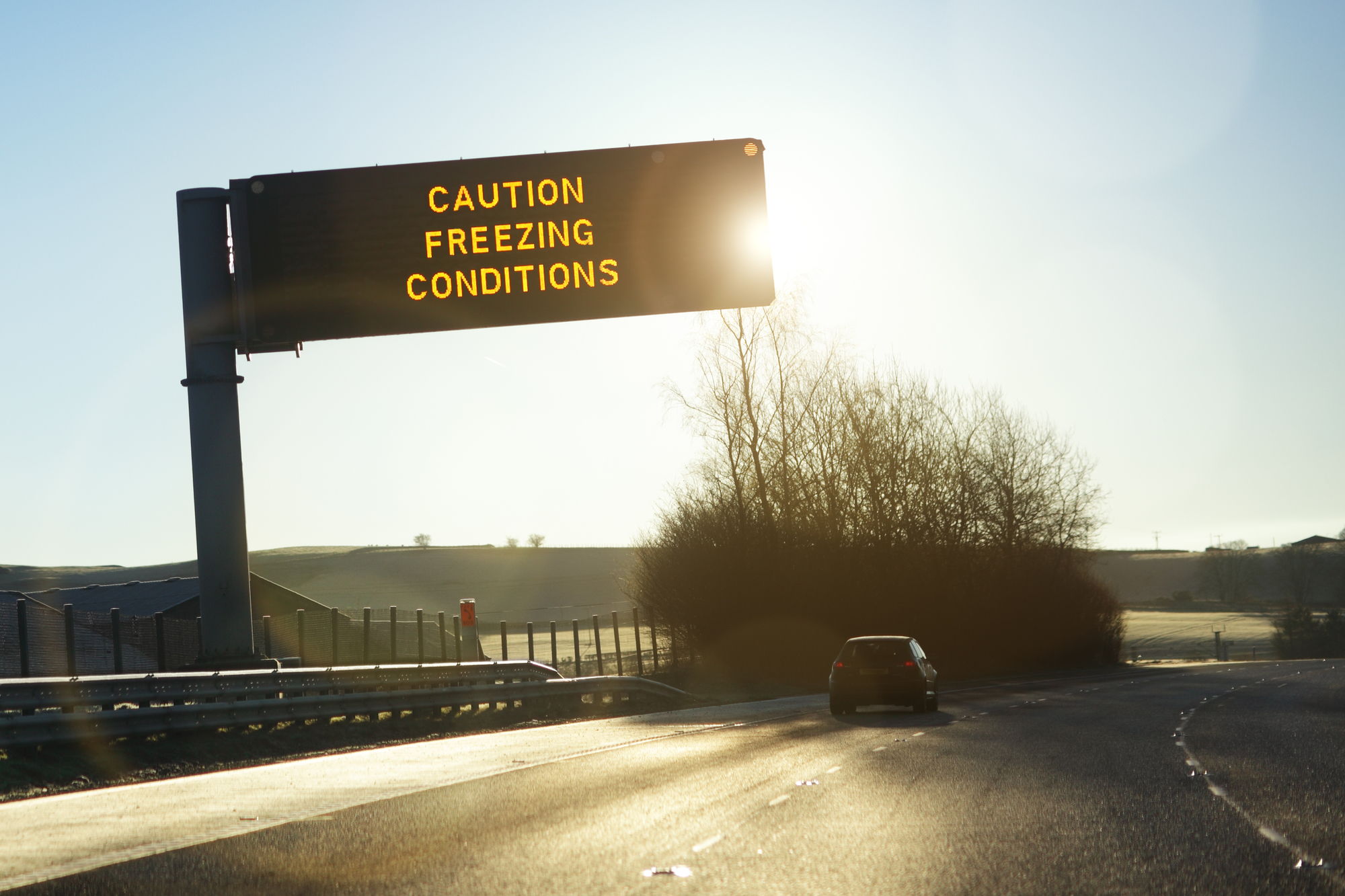 road sign in early morning winter sunshine reading caution freezing conditions