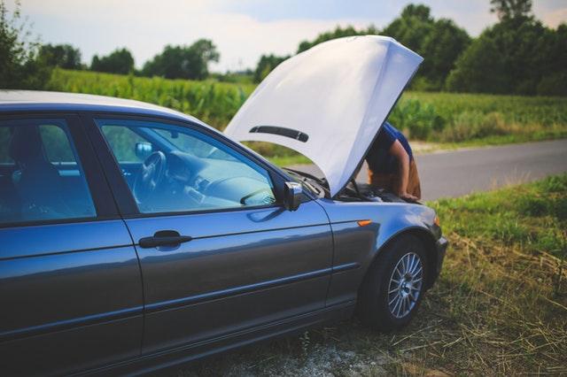 man leaning into hood of broken down car